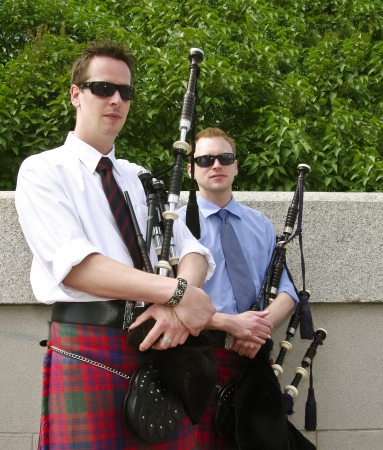 piper: Bagpipe duo relaxing between songs as they entertain tourists in Ottawa, Canada. Stock Photo