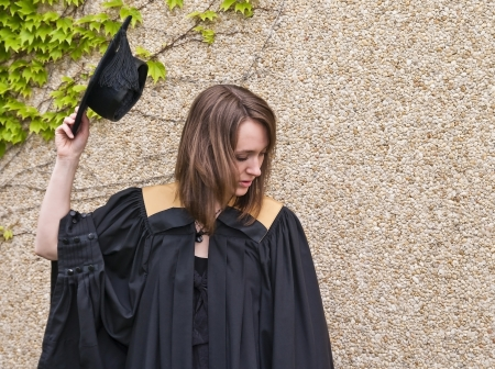 Young woman holding graduation hat against stone and leafy wall. photo
