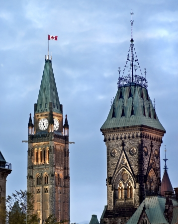 The Canadian Parliament Centre and East Blocks with the Maple Leaf flag in Ottawa, Ontario, Canada  photo
