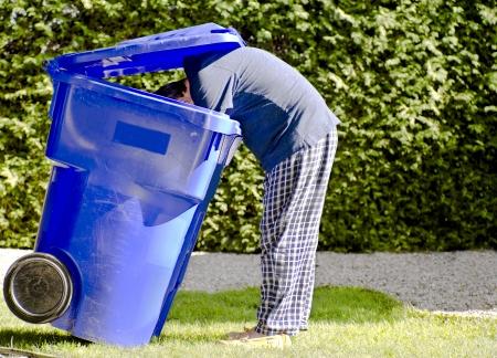 Man in pyjamas reaching inside a recycle blue bin to retrieve items