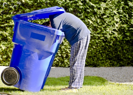 retrieve: Man in pyjamas reaching inside a recycle blue bin to retrieve items
