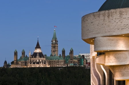 The canadian Parliament seen at dusk from the canadian civilization museum across the Ottawa river  photo