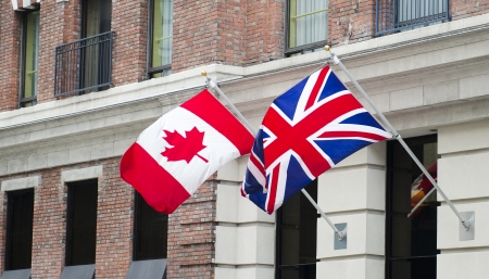 The Canadian and British flags waving proudly side by side  Stock Photo