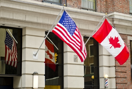 The Canadian and United States of America flags are waving proudly side by side in Ottawa, Canada
