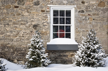 rural scenes: A heritage building window with evergreens in northern Canada during winter  Stock Photo