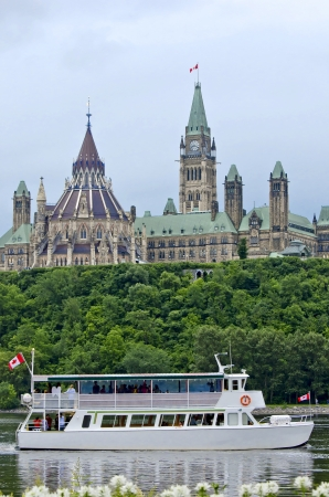 commons: The Canadian Parliament Centre Block and Library, overlooking a cruise boat on the Ottawa river during summer.