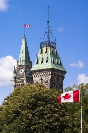 The Canadian Parliament Centre and East Block towers with Canadian flags waving in the wind during lunch hour in Ottawa. Stock Photo