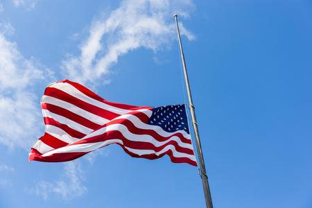 米国の旗は、半分のスタッフで飛ぶ 写真素材