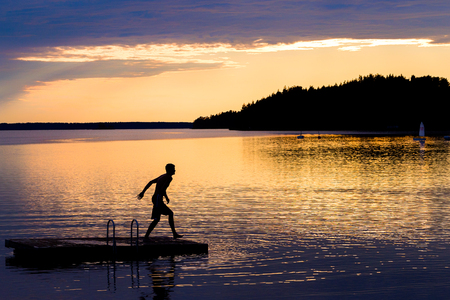 Silhouette of young man jumping from a pontoon into lake at sunset 版權商用圖片