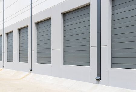 Empty warehouse loading dock white walls gray metal sliding doors
