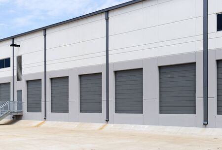 Empty warehouse loading dock white walls gray metal sliding doors Banque d'images