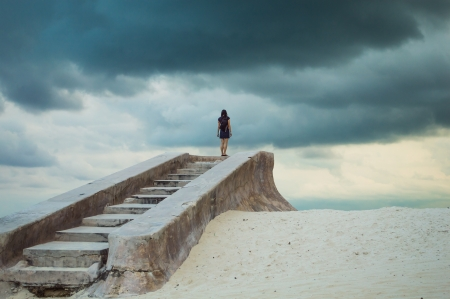 Stairs to nowhere; A female figure climbs a series of old forgotten stone steps on a deserted beach; Can convey a sense of isolation, depression, loneliness, hopelessness; Alternatively this could be viewed as hope eg after a 12-step program photo