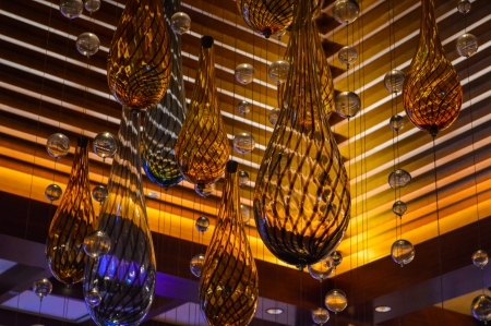 Abstract glass ornament chandelier against a textured wooden ceiling