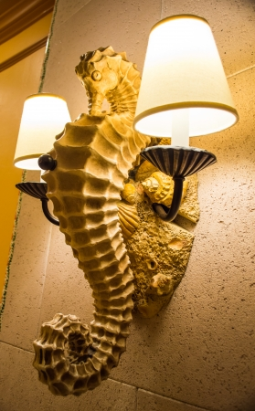 sconces: Seahorse wall lamp with metal lamp sconces, resting on background of shells Stock Photo