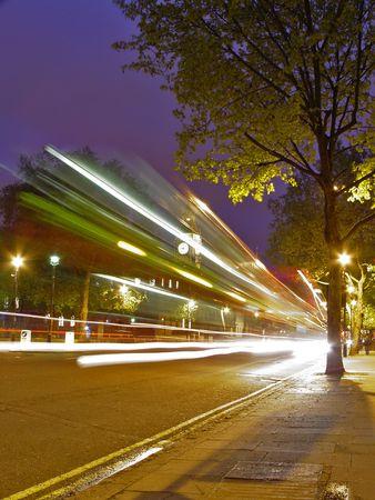 Speed blur of London red bus at Big Ben background at night  photo