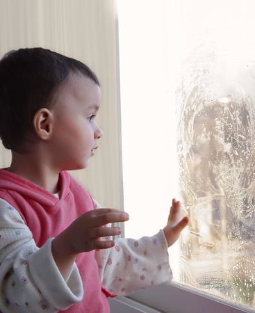 Little girl is touching wet window with her hand at sunny day Stock Photo - 5867988