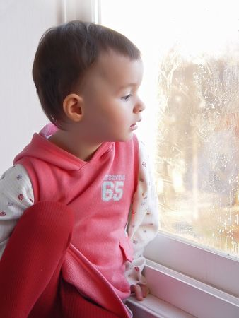 Little girl sitting near wet  window  at sunny day