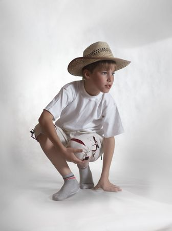 Sitting boy in straw hat on gray background looking right photo
