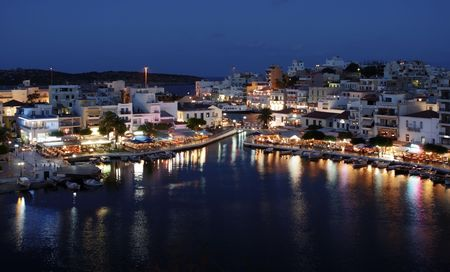 Night Panorama of Aghios Nikolaos, Crete, Greece. Old town, unique lake, marina, bay, restaurants. Stock Photo
