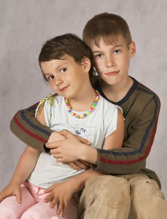 Brother hug a Sister Sitting On Couch Stock Photo