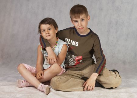 sister and brother sit at white background photo