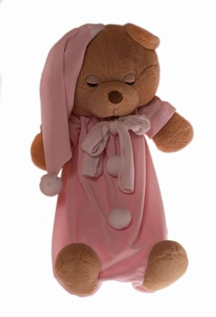 Isolated teddy bear slipping at white background. Soft children toy in pajamas