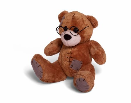 Isolated teddy bear sitting at white background. Soft children toy in glasses