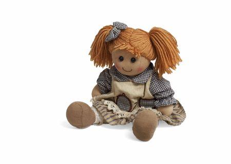 Izolowane lalka słodkie siedzi na białym tle. Zabawki miękkie dzieci