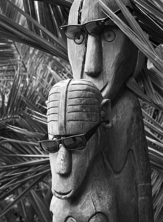 idols: Polynesian wooden idols in sunglas. Palm trees