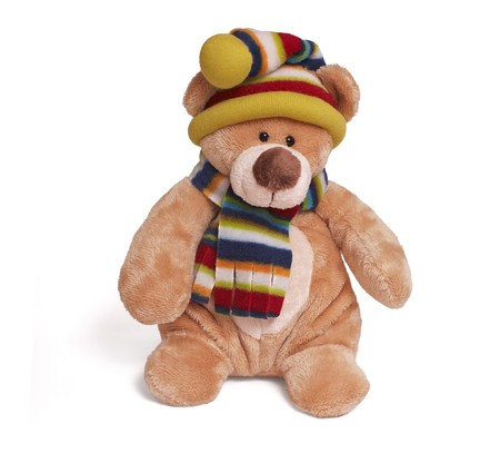 Isolated teddy bear sitting at white backgroung. Soft children toy in warm winter scarf and cap