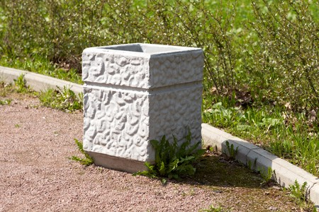 concrete trash urn on grass background Stock Photo