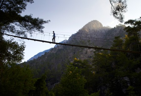 across: Boy om the suspension bridge in mountains forest