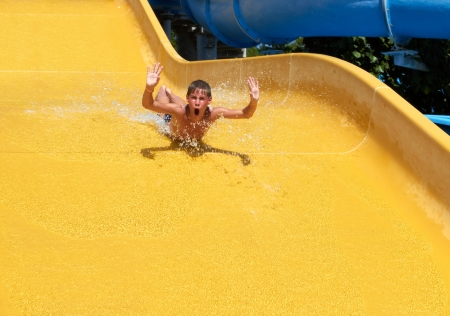 boy rolling with slide at water park photo