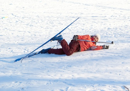 young beauty girl dropped on snow while skies