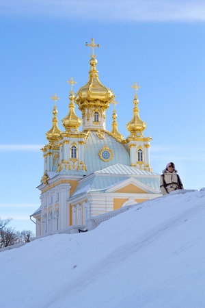petergof: young women near beautiful church in winer. Petergof, St. Petersburg, Russia