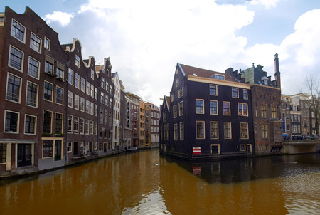 Old Houses and canals at Amsterdam center in cloudy day. Netherlands Editorial