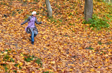 white girl run from the hill  in bright yellow autumn forest