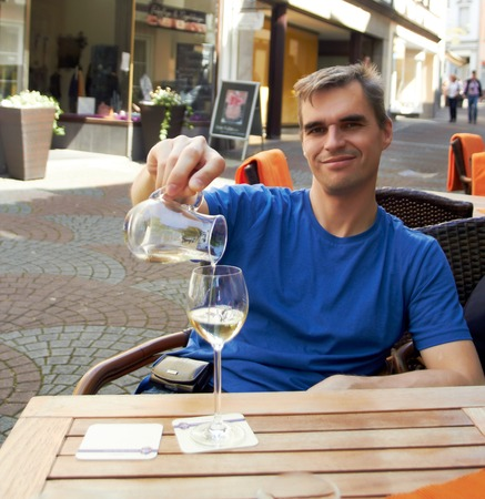 Man in a blue t-shirt filling a glas of white wine sitting in cafe Stock Photo
