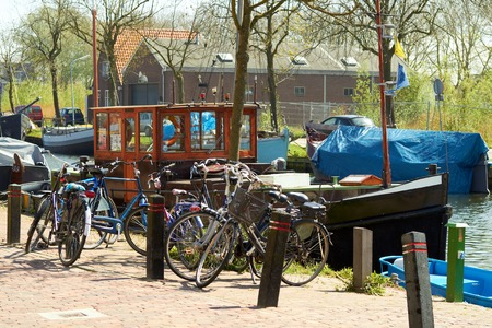 Bikes and Traditional Dutch Botter Fishing Boats in the small Harbor of the Historic Fishing Village in Netherlands.