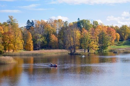 Autumn colorful landscape with vrssel boat and falling leaves.October day in Pavlovsk Park, St.Petersburg, Russia
