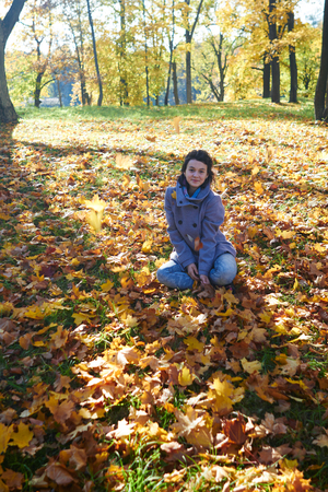 happy young teen girl in autumn scenery throwing leaves Stock Photo