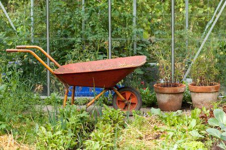 Wheelbarrow in front of  the greenhouse Archivio Fotografico