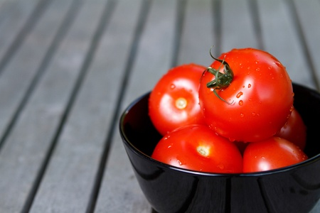 Tomatoes in black bowl Standard-Bild