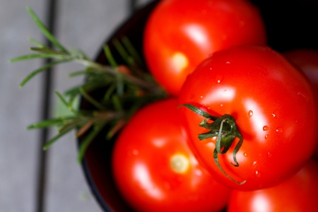 Tomatoes in black bowl with herbs