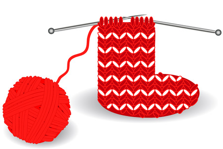 red-and-white Christmas sock on knitting needles and a tangle of red threads close to the holidays