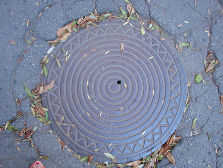 An old sewer manhole cover surrounded by an asphalt street