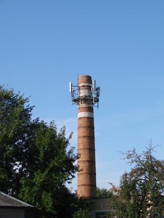 The old water tower is used as a cell tower. The concept of converting one into another, the use of explicit resources. Water Storage Tower and Cell Phone Signal Tower Against a Beautiful Blue Sky