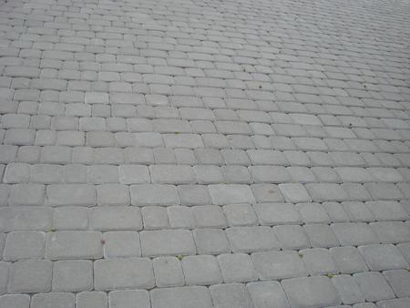 Stone pavement texture. Granite cobblestoned pavement background. Abstract background of old cobblestone pavement close-up. Archivio Fotografico