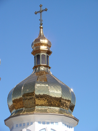 White Orthodox Church with big golden domes on a sunny day