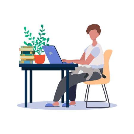 A man works at a laptop at home at a table. Freelance concept, quarantine due to covid-19.